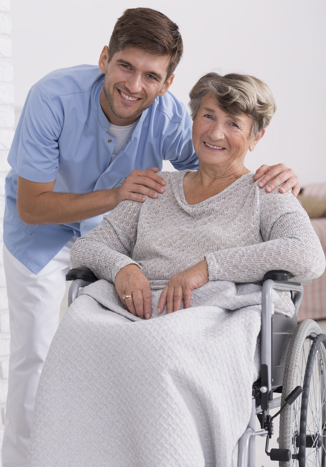 Shot of a young male carer and positive senior woman on a wheelchair, light background